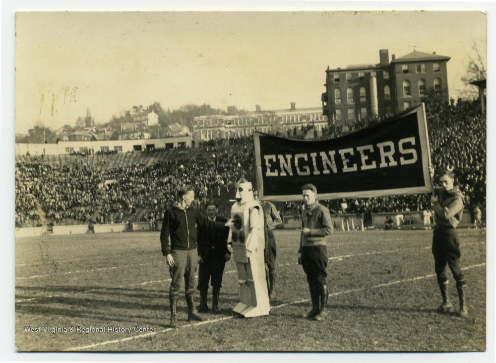 "Men on stadium field holding ""Engineers"" sign, with man in robot costume."