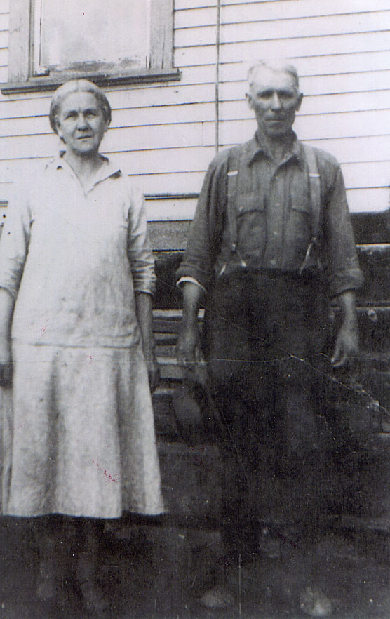 Woman and man standing in 1930s era casual clothing next to a house.