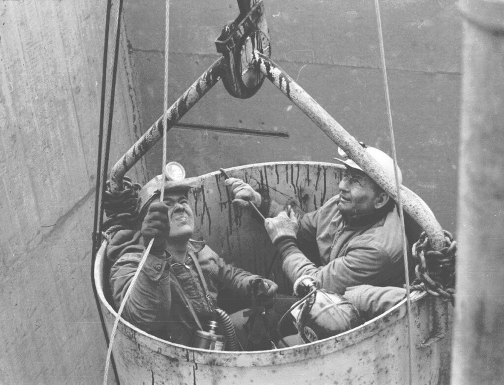 Three men in coal mining helmets, looking upwards from a bucket that is carrying them up a shaft