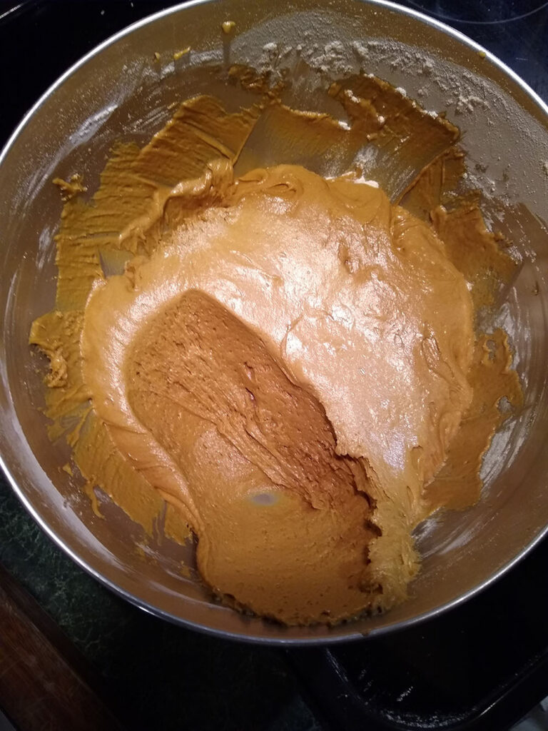 Bowl of brown cake batter with a scoop taken out.