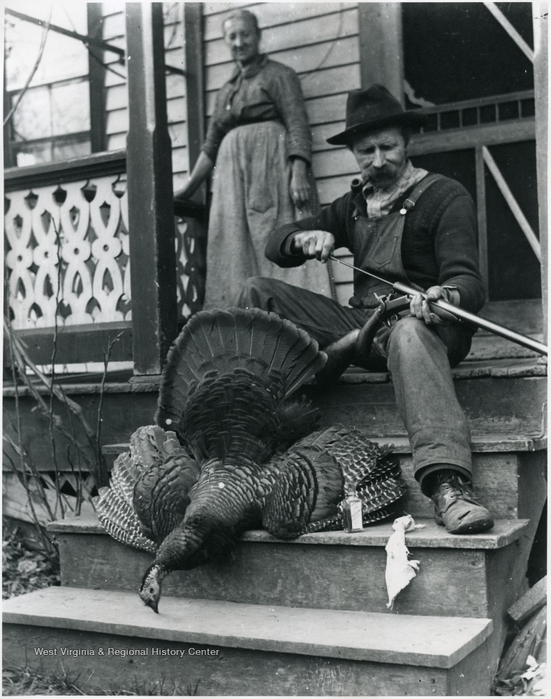 Woman standing on porch next to seated man who is cleaning his gun. A dead turkey is displayed at his feet.