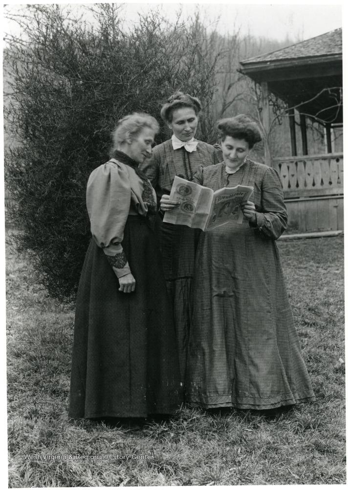Photo of three women standing outdoors around a newspaper.