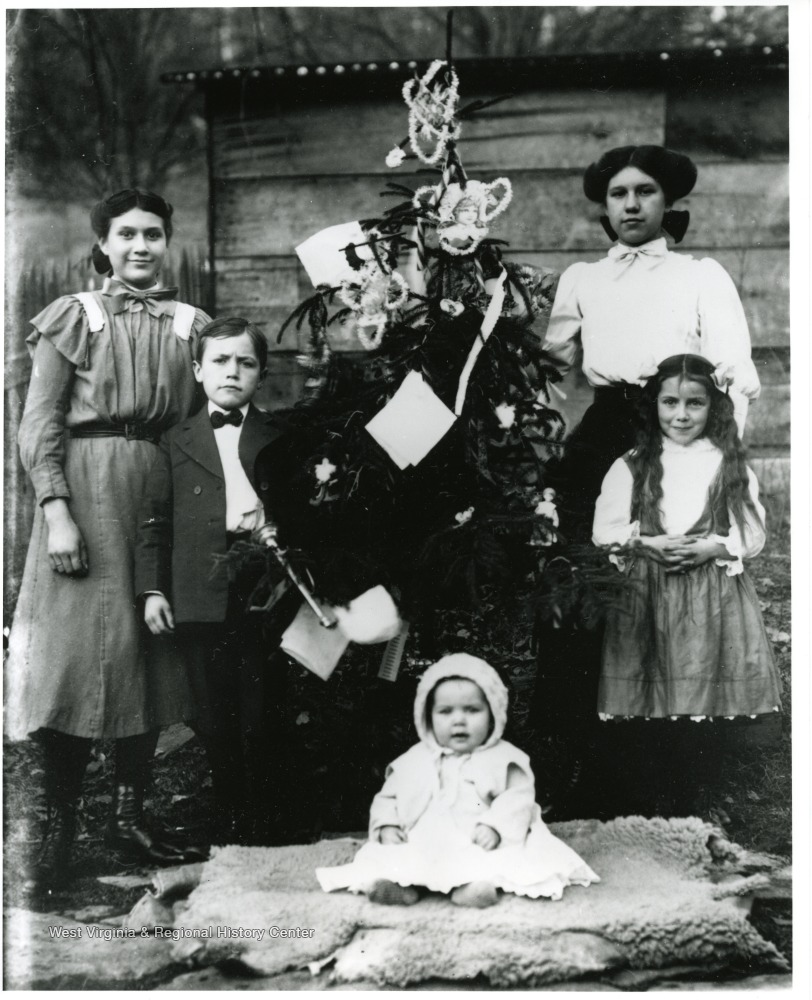 Photo of five children of various ages, arranged around a decorated Christmas tree.
