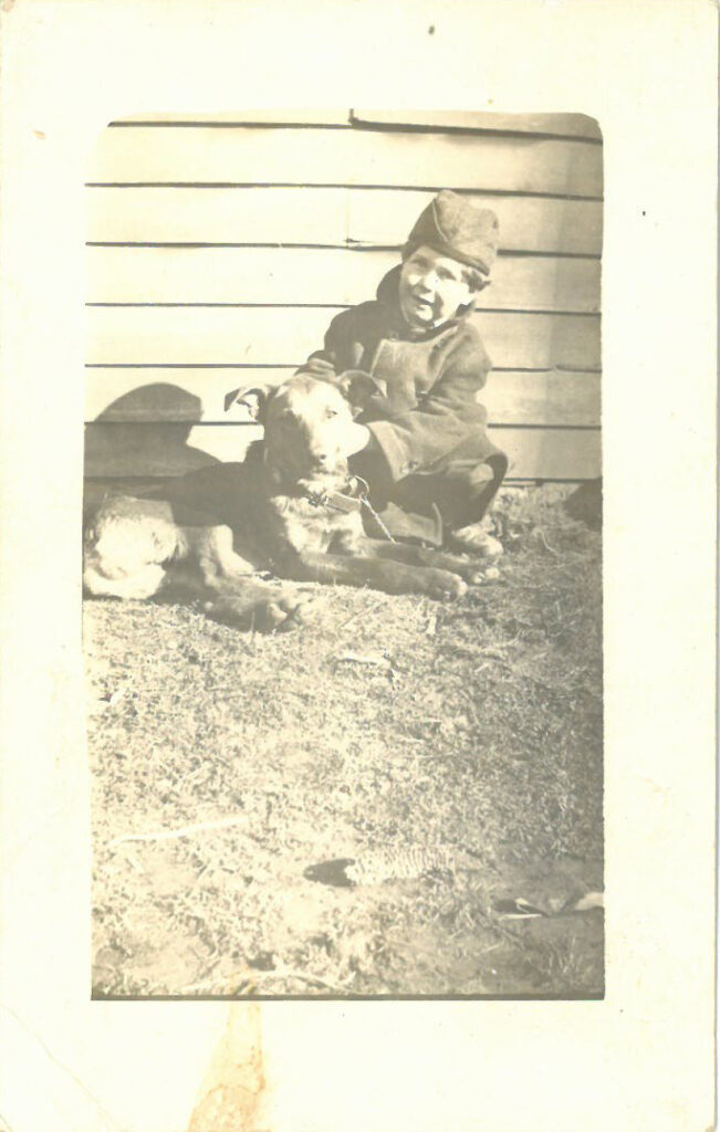 Boy seated next to dog, outside a house