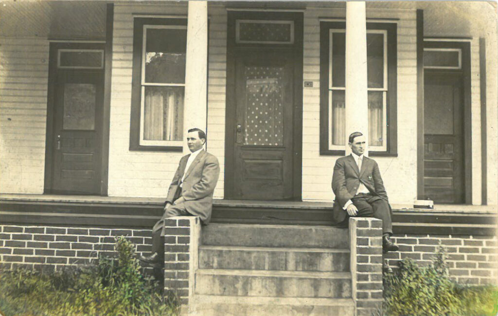 Two men seated at pillars on opposite sides of a residential front door
