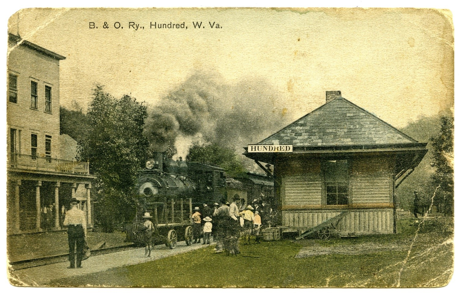 Small train depot, train track with train, and unidentified building