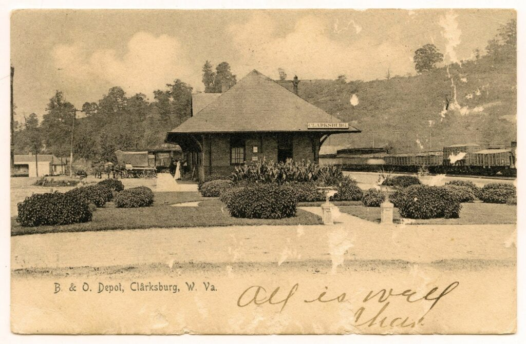 Train depot with people clustered out front, surrounded by landscaped bushes