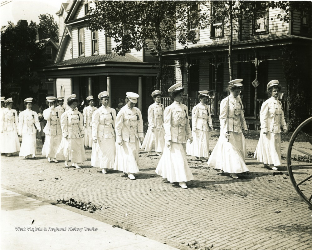 Women in white hats, jackets, and skirts march down a cobblestone street.