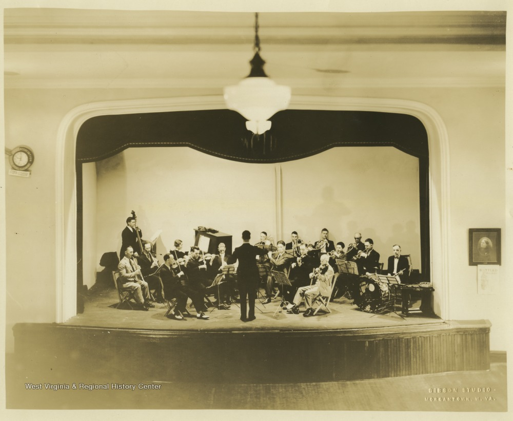 Proscenium style theatre with bad and conductor on the stage