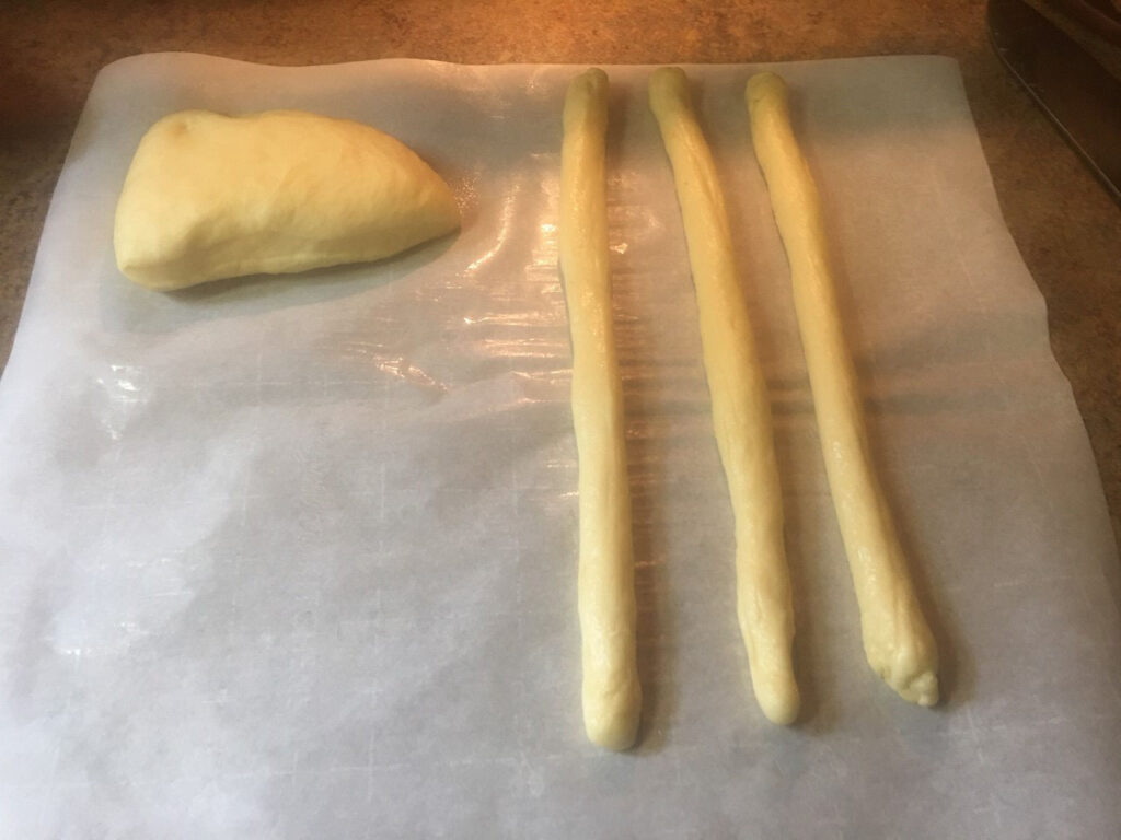 Strips of dough and ball of dough on wax paper.
