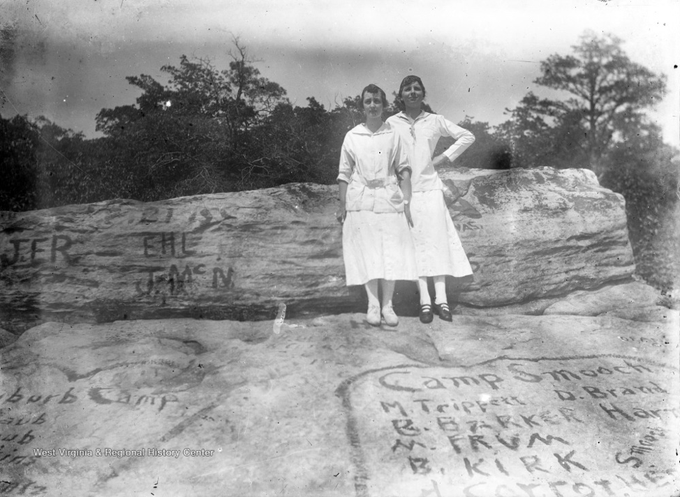 Two Girls on Graffiti Covered Rock