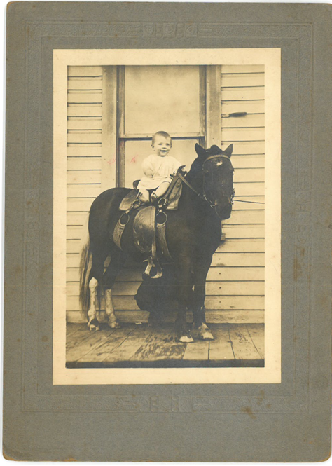 Smiling baby seated on a pony