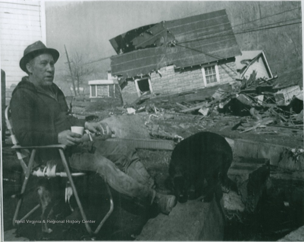 Man sitting in front of a house that has been swept off its foundation by a flood