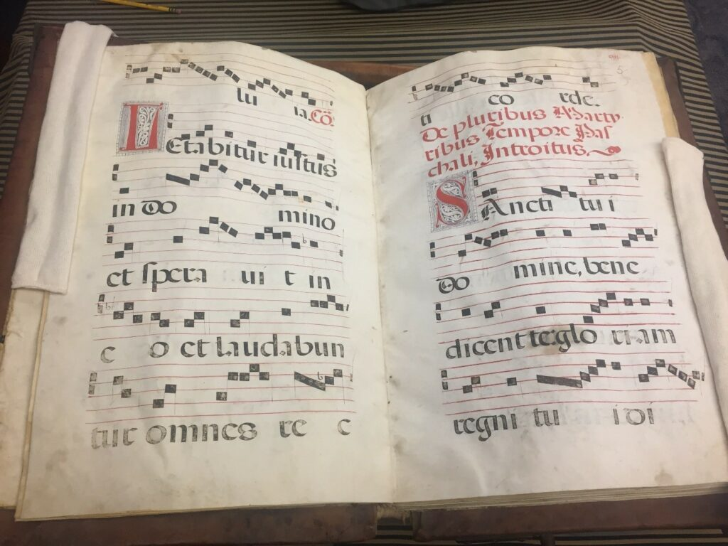 Pages of a book with musical notation and Latin text