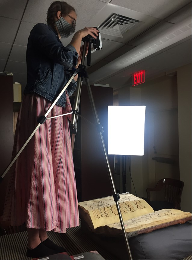 Woman operating camera on tripod to photograph a book