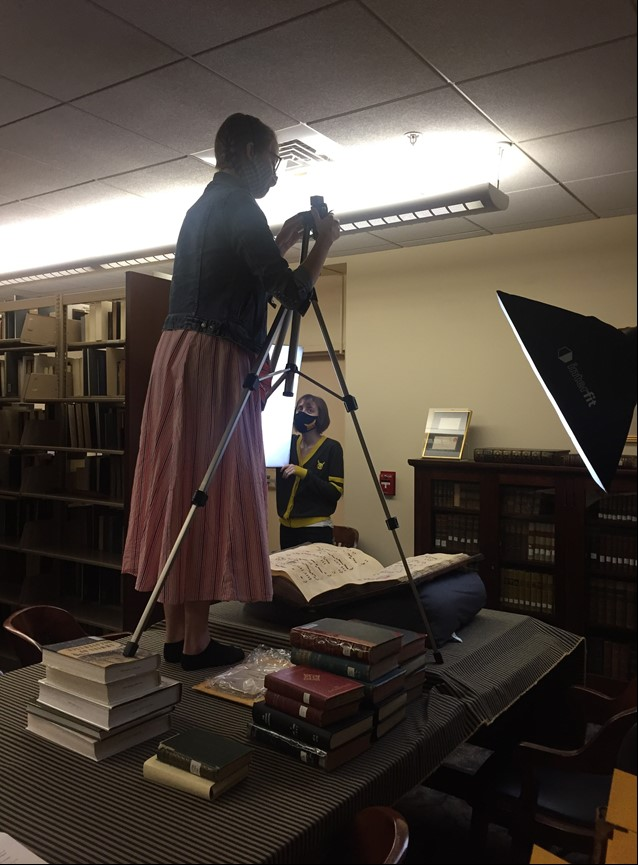 Woman operating camera on tripod to photograph a book as another woman looks on
