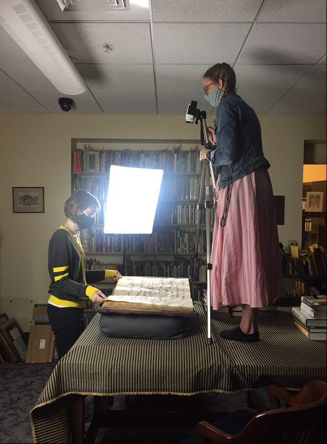 Woman operating camera on tripod to photograph a book as another woman turns pages