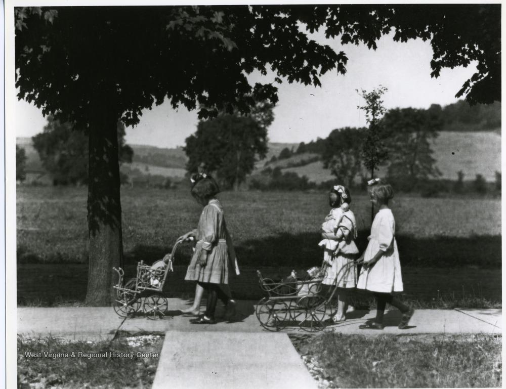 Little girls pushing dolls in prams.