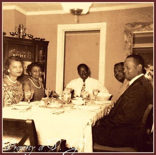 Five well-dressed African Americans sit around a fancy dining table having a meal.