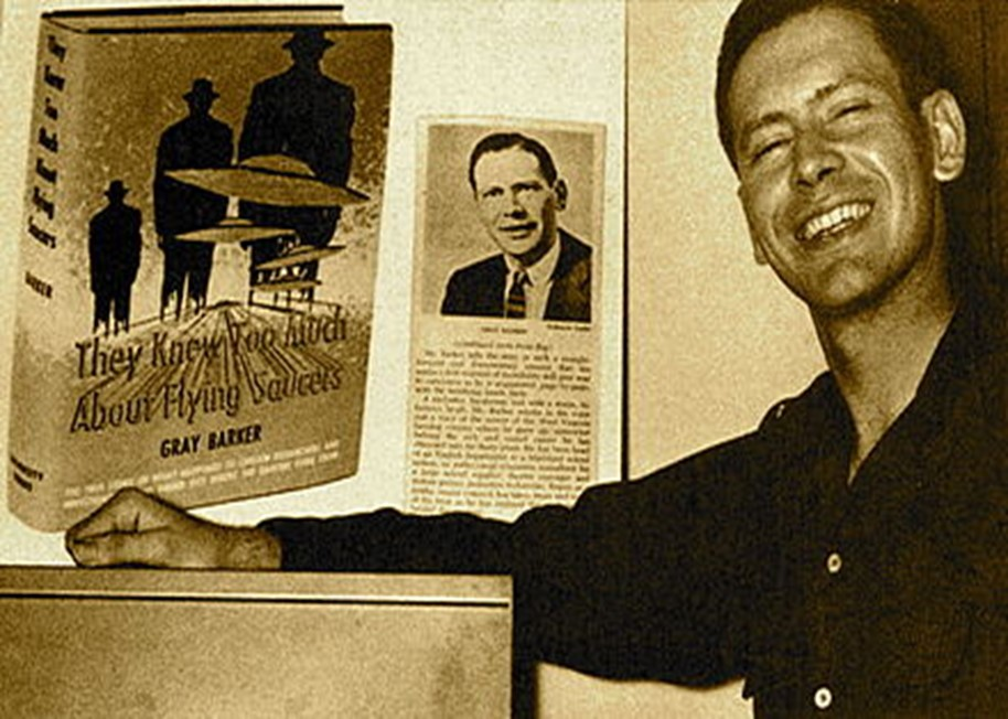 """Gray Barker smiling next to the cover of his book, """"They Knew Too Much about Flying Saucers."""""""