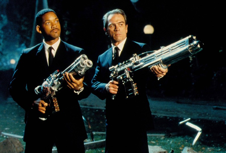 """Will Smith and Tommy Lee Jones in """"Men in Black"""" posing with blaster guns."""