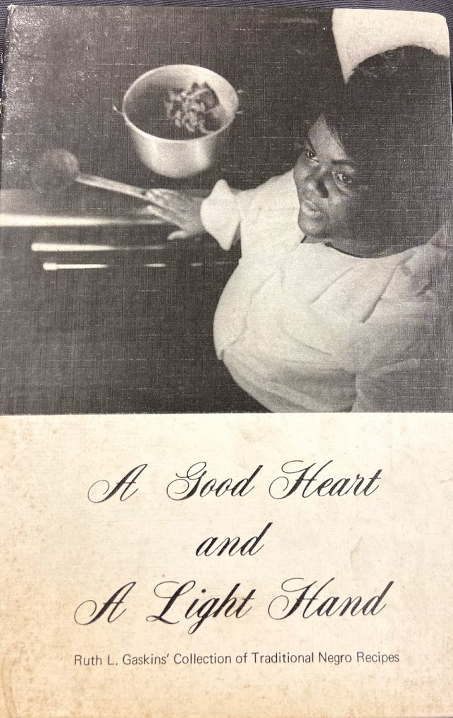 Cover of A Good Heart and A Light Hand: Ruth L. Gaskins' Collection of Traditional Negro Recipes. Features a black and white photo of Ruth L. Gaskins standing beside a full pan on a stove