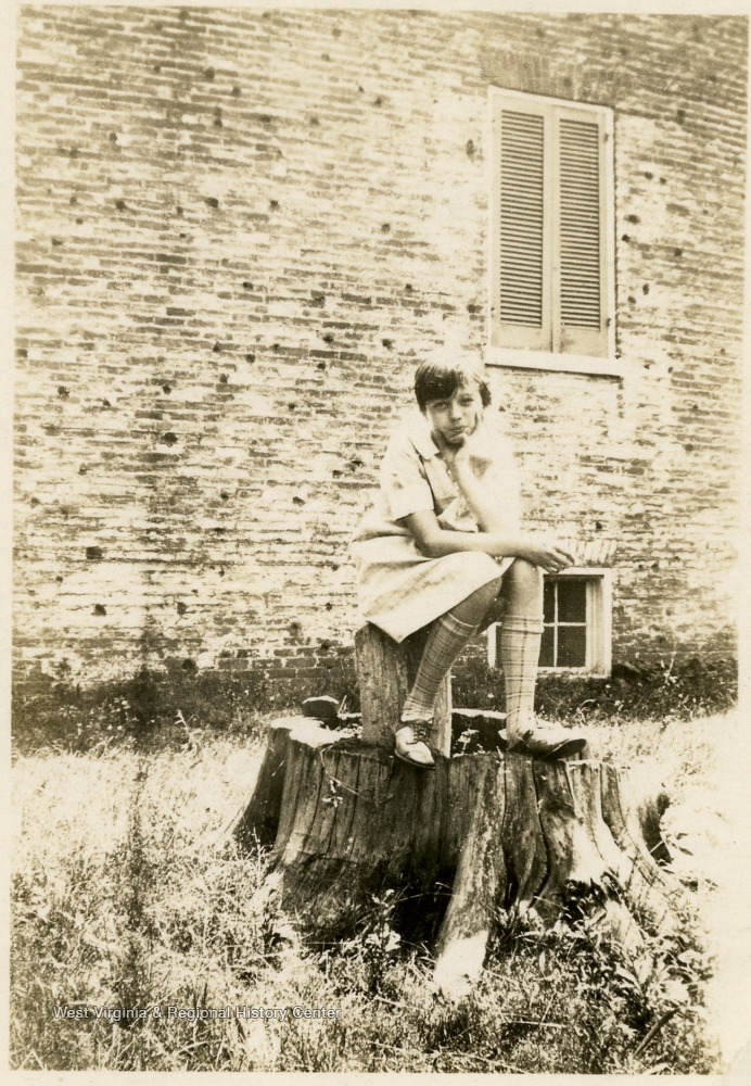 Girl seated on stump, with bullet holes visible in the brickwork of the building behind her