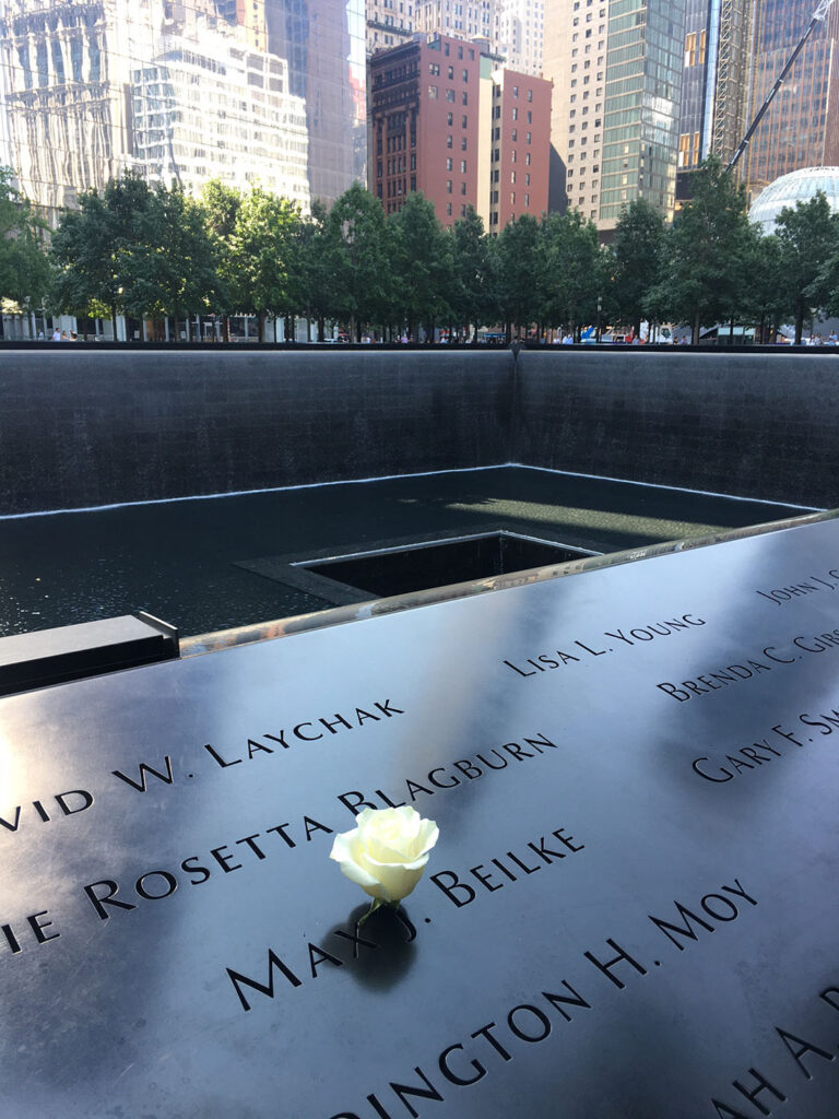 White rose placed in a name on the plaque along the border of a reflecting pool at the National 9/11 Memorial and Museum